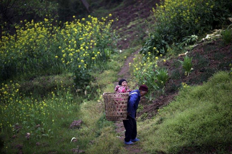 一名中國婦人於重慶市郊揹著孩子(美聯社)
