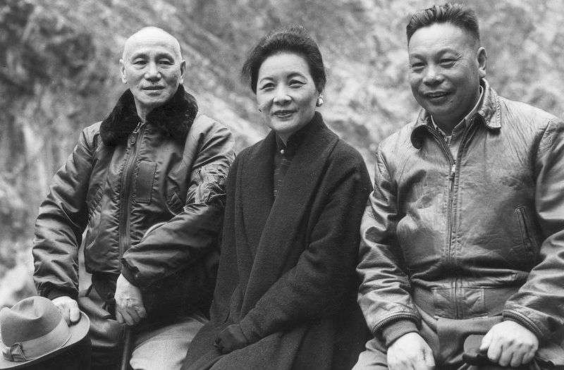 1955前後,宋美齡與蔣介石、蔣經國父子坐在石牆上。(Getty/Hulton Archive)