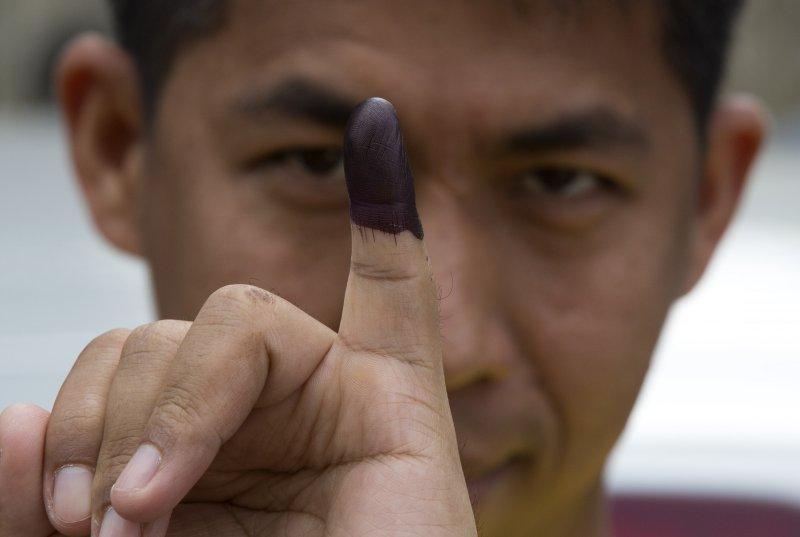 緬甸11月8日舉行國會選舉,一位選民秀出投票後沾有墨水印記的小指。(美聯社)