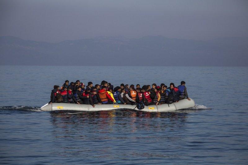 搭船靠近希臘萊羅斯島的難民(美聯社)
