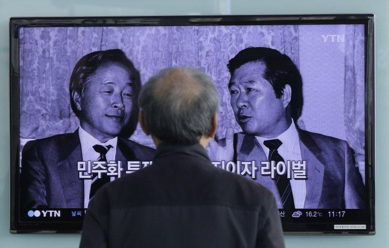 南韓前總統金泳三病逝,民眾觀看電視新聞報導,畫面中左為金泳三,右為與他亦友亦敵的金大中(美聯社)