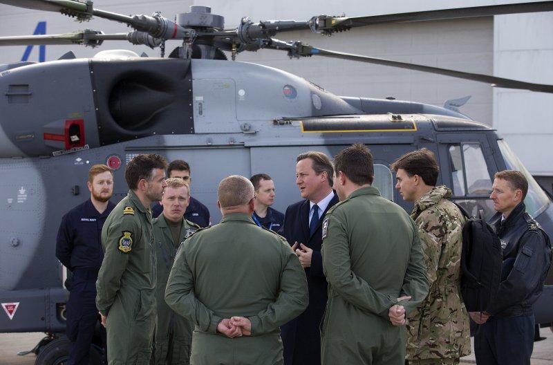 英國首相卡麥隆(中著西裝者)23日視察英國皇家空軍。(美聯社)