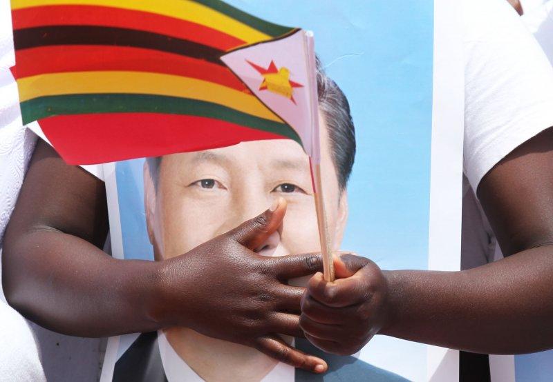 辛巴威人民抱著中國國家主席習近平的照片。(美聯社)