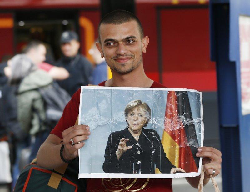 一名難民抵達慕尼黑車站時舉起梅克爾照片(美聯社)