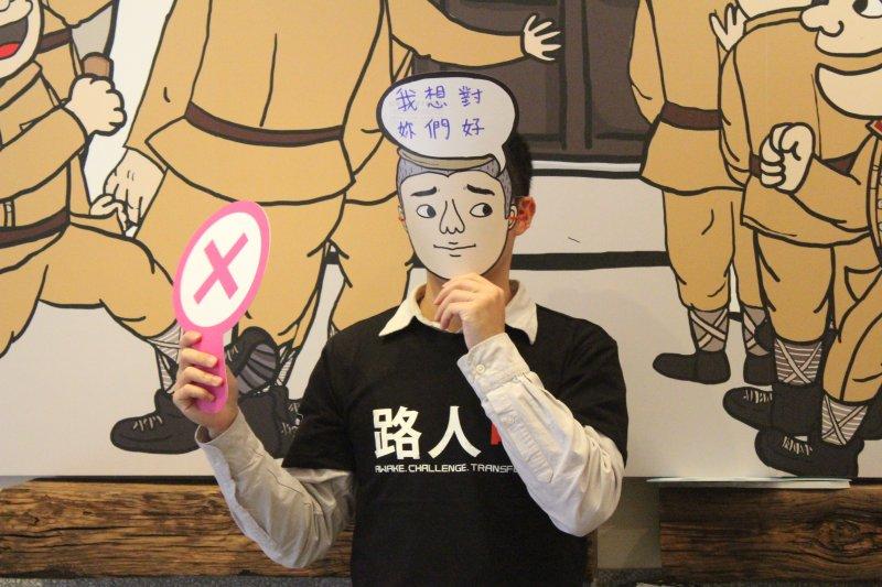 工作人員現場示範,體會日本軍人情境。工作人員手舉叉叉牌子,表示不會使用慰安卷、保險套。(廖欣俞攝)