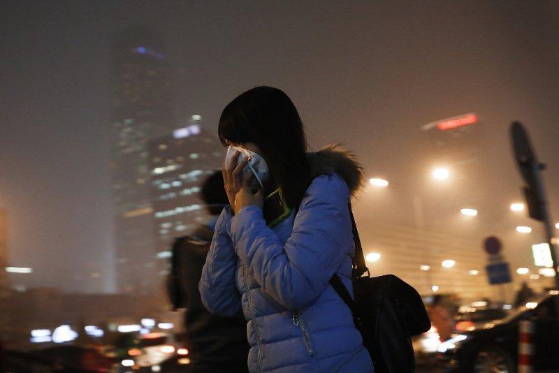 中國女子掩蓋口鼻減輕汙染影響(美聯社)