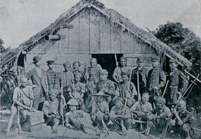 石門戰役後,日軍指揮官西鄉從道與排灣族領袖合影。左坐者為卓杞篤、中坐者為西鄉、右坐者為一色。(維基百科)