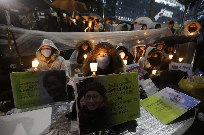 南韓學生於30日手持前慰安婦照片參與示威活動(美聯社)