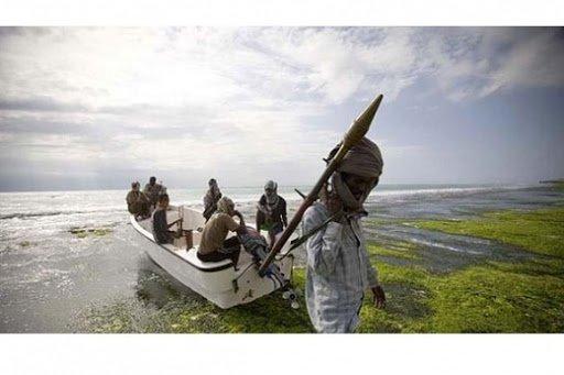 索馬利亞海盜扛著一枚火箭彈,身後小船上坐著他的同夥。這個海盜集團名為「中部地區海岸巡邏隊」,成立於2005年。(取自網路)