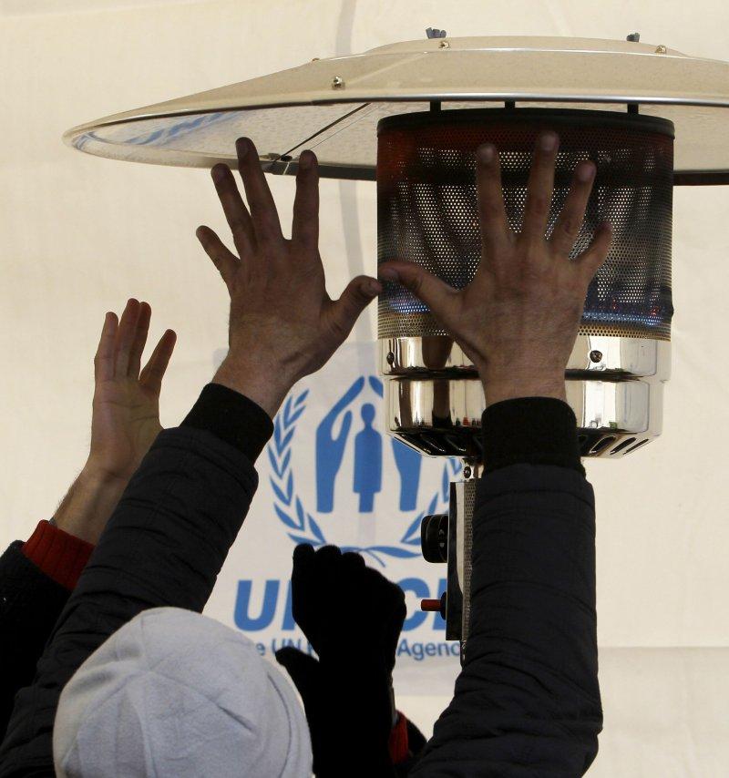 難民圍著聯合國救難機構的火爐取暖。(美聯社)