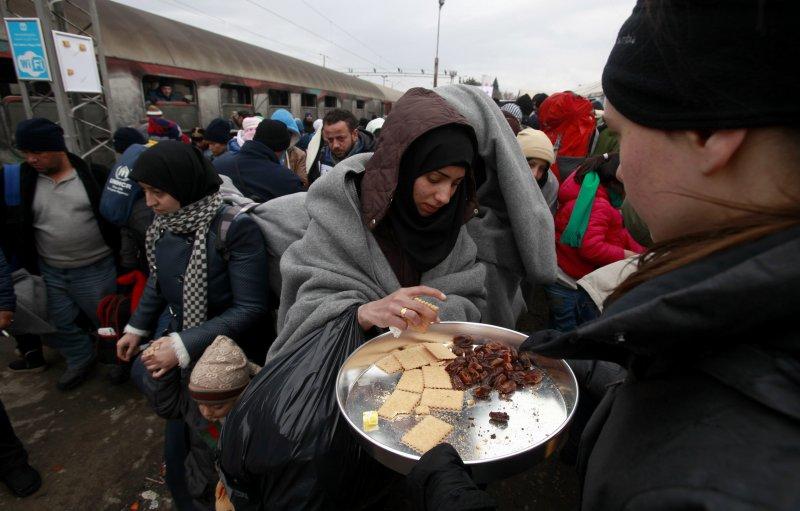 難民從人道團體手中接過食物(美聯社)