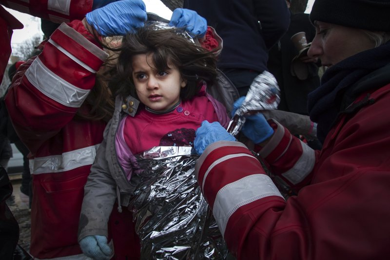 慈善團體的成員正在為一名剛上岸的小女孩穿上防寒衣(美聯社)