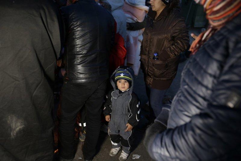 一名男童移民與其他移民一同在希臘一處難民營取暖(美聯社)