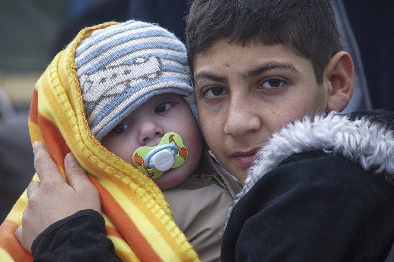 一名男孩抱著嬰孩,1月29日自土耳其抵達希臘(美聯社)