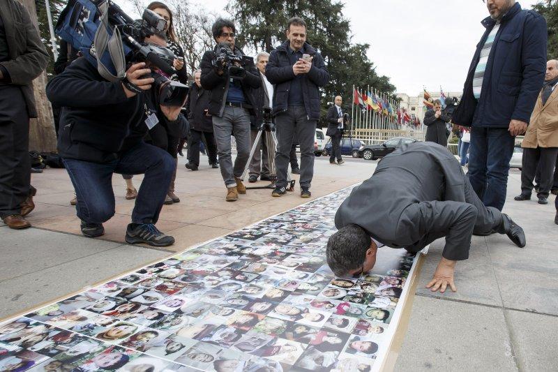 萬國宮外展示著敘利亞內戰罹難者的照片,HNC的發言人跪下來親吻這些照片(美聯社)