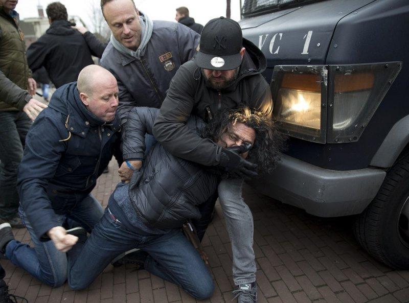 便衣警察拘留一名參與阿姆斯特丹示威的民眾(美聯社)