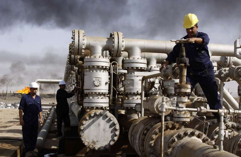 伊拉克油田工人正在操作油管。(美聯社)