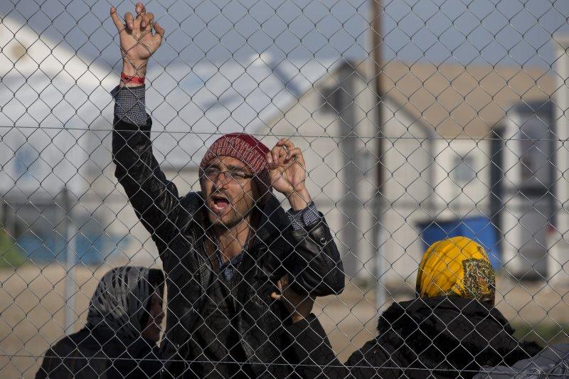 一名阿富汗難民/移民在希臘邊界大喊:「梅克爾救救我們!」(美聯社)