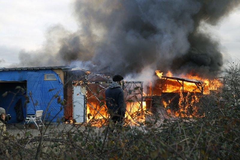 一名移民看著燃燒的搭建屋(美聯社)