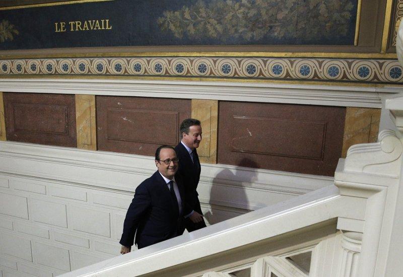 法國總統奧朗德與英國首相卡麥隆抵達記者會(美聯社)
