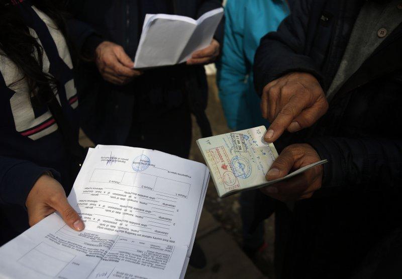 難民拿出庇護申請文件及護照(美聯社)