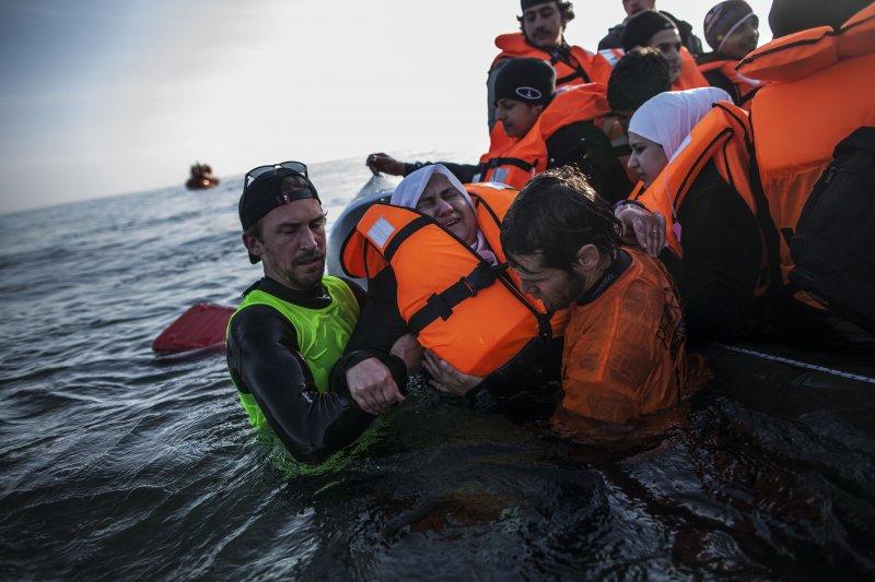 救難人員正在協助一名敘利亞難民(美聯社)