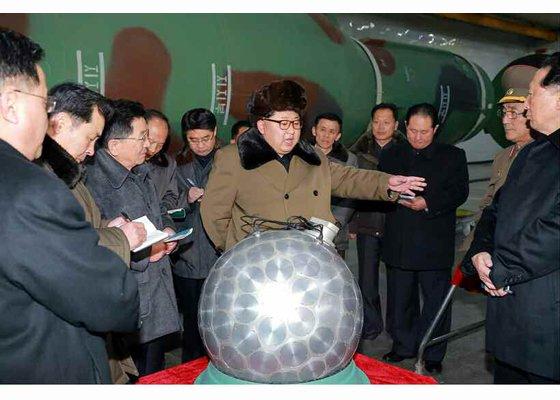 北韓領導人金正恩視察小型化的核彈頭。(勞動新聞)