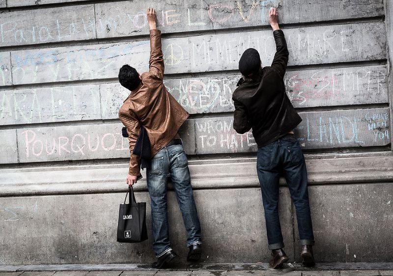 比利時恐攻,2名男子在布魯塞爾牆上留下給受害者的紀念(美聯社)
