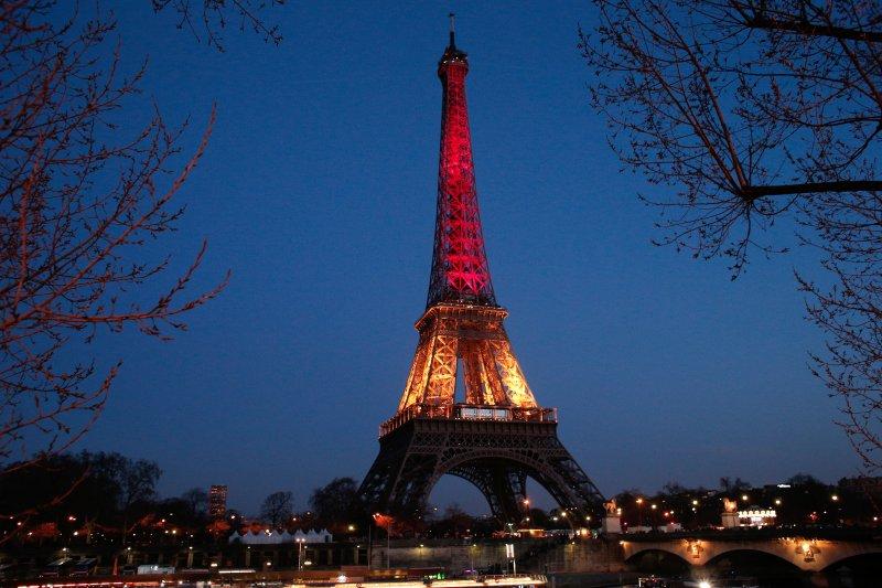 巴黎艾菲爾鐵塔22日晚間亮起象徵比利時國旗的黑、黃、紅3色(美聯社)