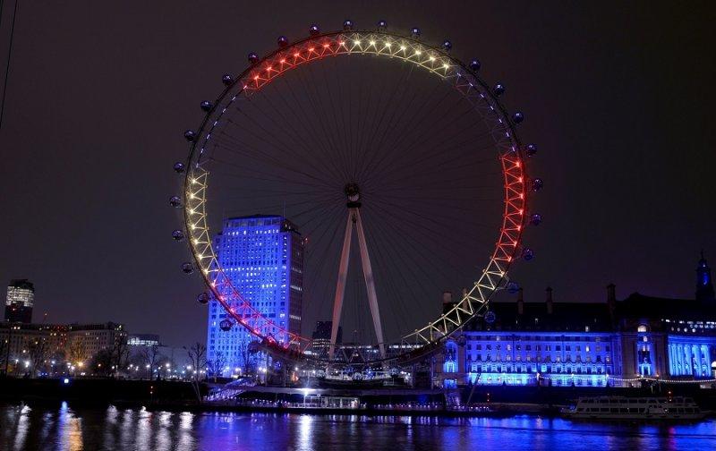英國倫敦眼23日亮起象徵比利時國旗的紅、黃、黑三色(美聯社)