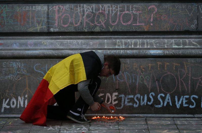 一名男子身披比利時國旗,為恐攻遇難民眾哀悼(美聯社)