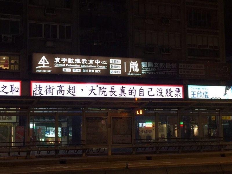 台北市大安區大安捷運站旁有民眾購買電子看板當「對聯」,以「中研院之恥」、「技術高超、大院長自己真的沒股票」等詞語諷刺翁啟惠。(讀者提供)