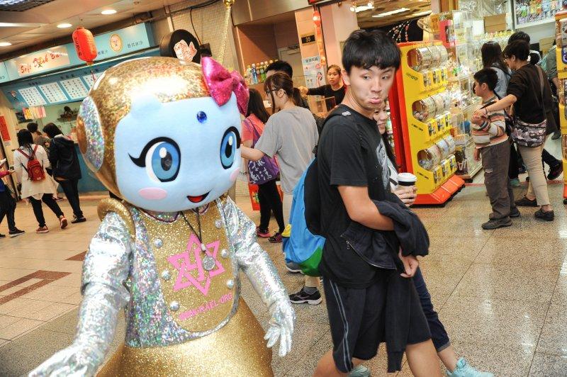 台灣雷爾運動組織3日於台北地下街舉辦說明活動,好奇的民眾路過對外星人偶做出怪表情。(林俊耀攝)