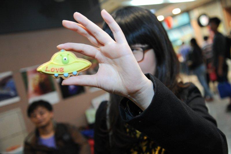 台灣雷爾運動組織3日於台北地下街舉辦說明活動,現場發放可愛的外星人餅乾。(林俊耀攝)