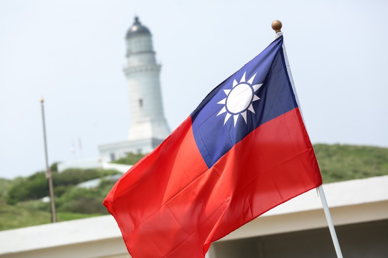 飄揚的中華民國國旗,與島上的彭佳嶼燈塔相互輝映。(顏麟宇攝)