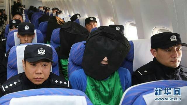 肯亞詐騙案中中國強擄45名台灣人事件,第二批37名台灣人及中國嫌犯已遣返抵達北京機場,涉案嫌犯皆被戴上黑色頭套。(新華社)
