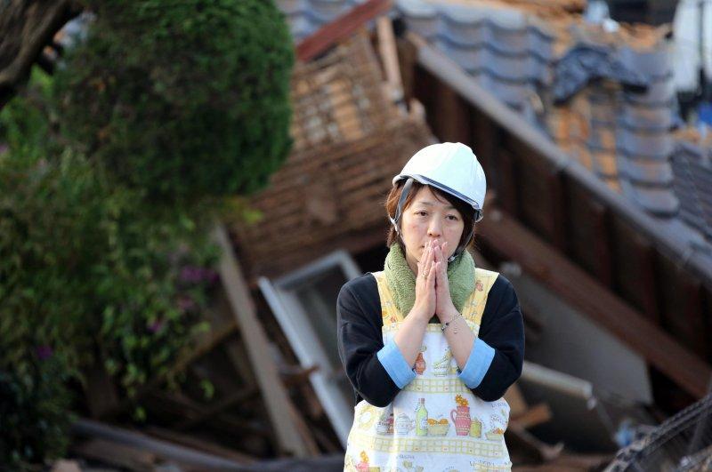 一名女子站在熊本縣益城町被震毀的民宅前,雙手合十。(美聯社)