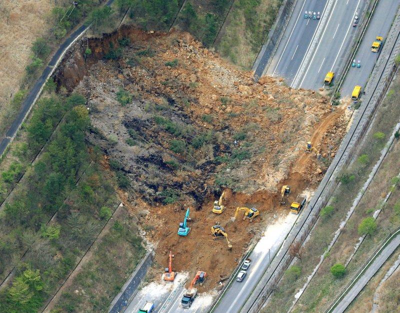地震引發山崩,造成大分縣的高速公路嚴重受損,當地出動怪手搶修。(美聯社)