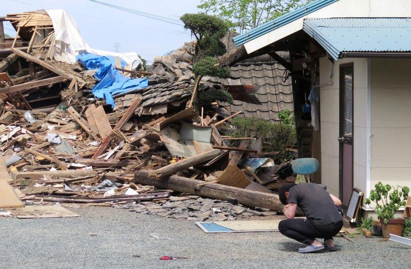 益城町的一名男子得知母親被困在倒塌的民宅中,忍不住掩面跪下(美聯社)