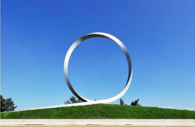 藝術家邱文傑的《迴》,設立在華航園區前,作品以約1000片鑄鋁合金版,緊扣拼出圓形環轉的概念,擬倣繞行地球總共360°的經度。起點即是終點,彷彿是在訴說旅程往返的本質皆不過如此。(圖/桃園機場提供)