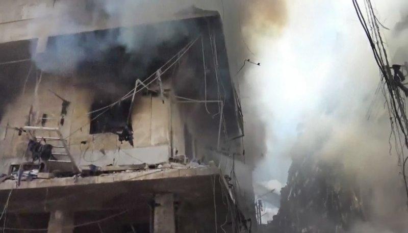 阿勒波遭受空襲後建築起火冒煙(美聯社)
