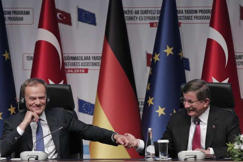 歐洲理事會主席圖斯克(左)與土耳其總理達武特奧盧(右)在記者會上攜手(美聯社)