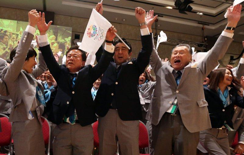 獲知東京申奧成功時,包括日本首相(中)的代表團成員都起立歡呼。(美聯社)
