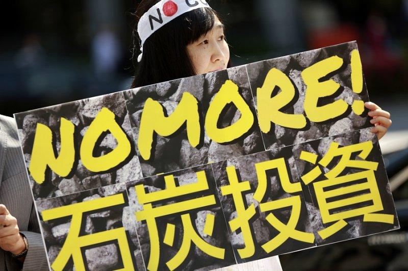 19日,一名女性在日本東京G7會議間抗議煤業投資(美聯社)