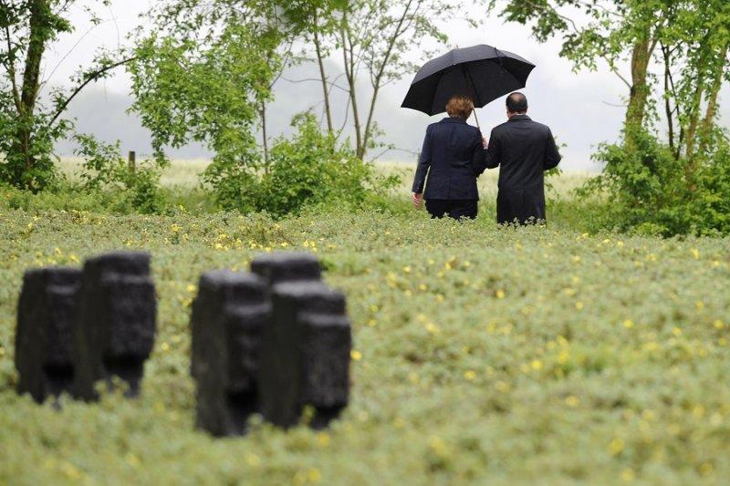 法國總統奧朗德與德國總理梅克爾共撐一把傘(美聯社)
