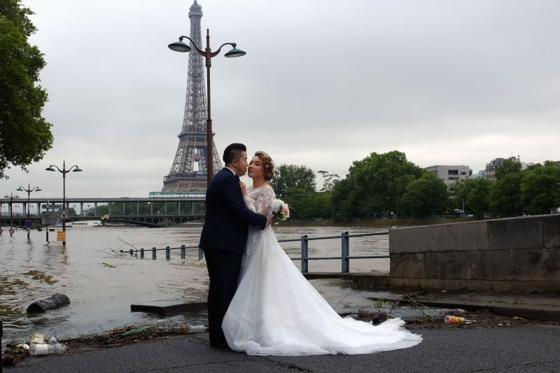 一對新人在艾菲爾鐵塔前取景。(美聯社)