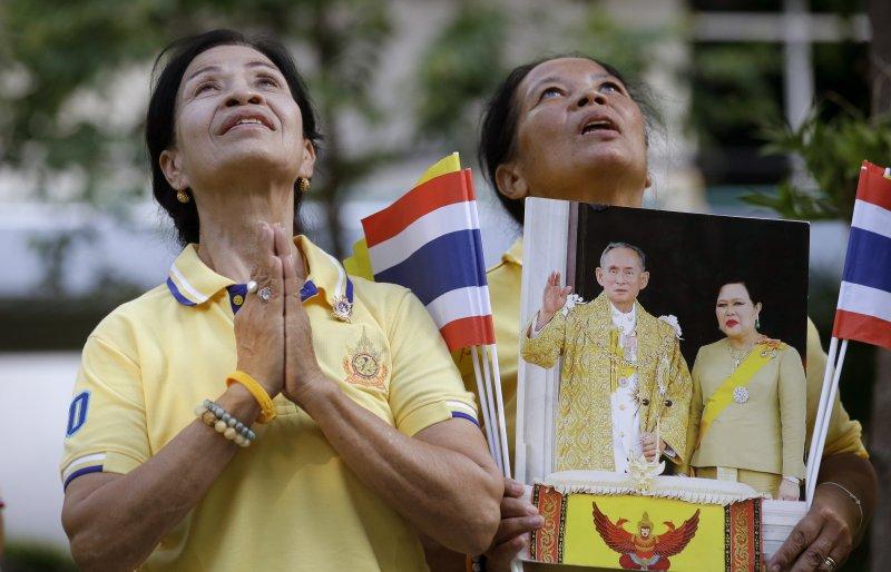 泰國民眾手持國王與王后的照片為其祝禱。(美聯社)