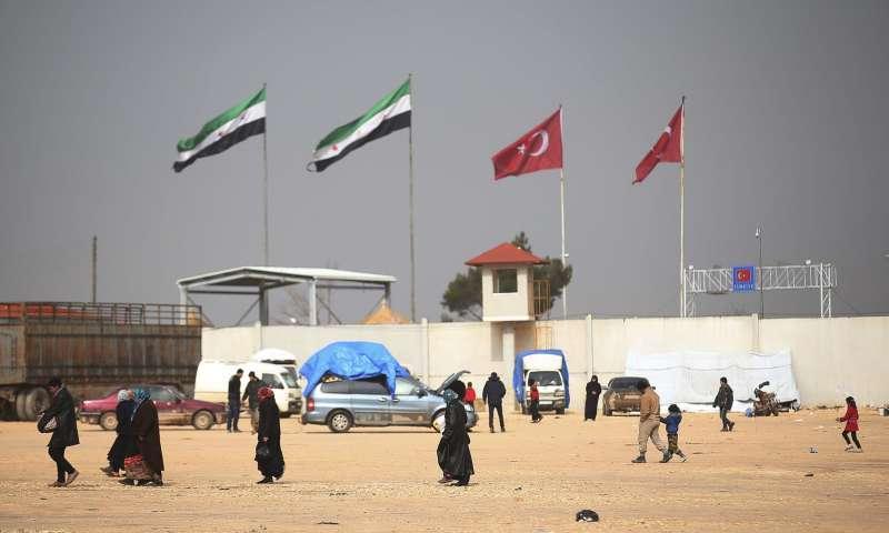 正通過土敘邊境,進入土耳其國境的敘利亞難民。(美聯社)