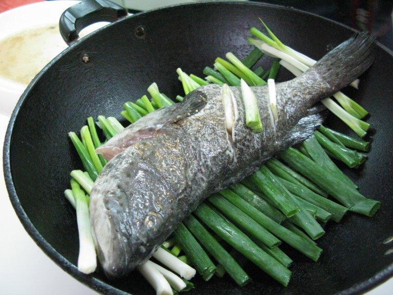 何麗玲利用青蔥墊底來蒸魚。(圖/皇冠文化提供)