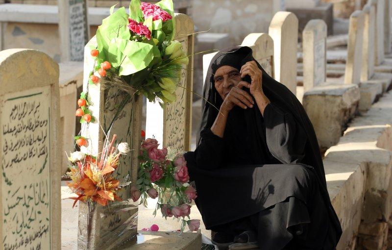 這名伊拉克婦女來到兒子墳前獻花,兒子死於兩天前的巴格達爆炸案。(美聯社)